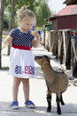 Little girl and billy goat eating ice cream being followed by Stock Images