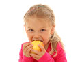 Little girl bites in an apple isolated over white background Royalty Free Stock Images