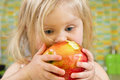 Little girl biting an apple Royalty Free Stock Photo