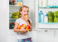 Little girl biting apple near fridge Royalty Free Stock Photo