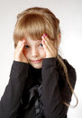Little girl in a black dress shuts face with the hands Stock Photography