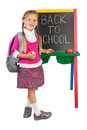 Little girl at a blackboard schoolgirl standing next to the with the back to school message on it isolated Stock Photo