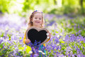 Little girl with blank board in flower field Royalty Free Stock Photo