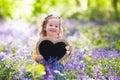Little girl with blank board in flower field Royalty Free Stock Photo
