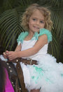 Little girl blond hair blue eyes wearing turquoise white princess dress white ruffle having fun riding pony strapped to saddle Stock Images