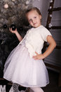 Little girl with blond hair wear elegant dress,posing beside Christmas tree Royalty Free Stock Photo