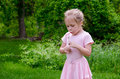 Little girl blowing dandelion fluff a in pink blows Stock Image