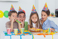 Little girl blowing her candles during her birthday party with parents and brother Stock Image