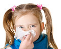 Little girl blowing her nose in a great effort closeup isolated Stock Image