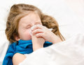 Little girl blowing her nose lying in the bed Stock Image