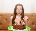 Little girl blowing out the candles on a birthday cake Royalty Free Stock Photo