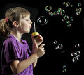 Little girl blowing soap bubbles Stock Photos