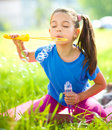 Little girl is blowing a soap bubbles cute Stock Photography