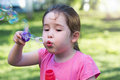 A little girl blowing soap bubbles in a park Royalty Free Stock Photo
