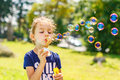 A little girl blowing soap bubbles in summer park. Royalty Free Stock Photo