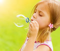 Little girl blowing soap bubbles sweet in the garden summer time game outdoors having fun holiday concept Stock Photo