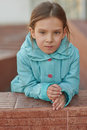 Little girl in blue jacket beautiful around school building Stock Photo