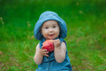 Little girl in blue jeans and a hat on his head in a blue dress Royalty Free Stock Photo