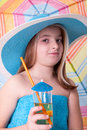 Little girl in blue summer hat drinking juice beautiful Royalty Free Stock Photography
