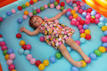 Little girl in a bouncy castle surrounded by colourful balls on the floor Royalty Free Stock Photography