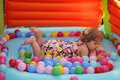 Little girl in a bouncy castle surrounded by colourful balls on the floor Stock Images