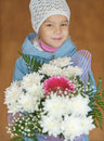 Little girl with bouquet of flowers beautiful on brown background Stock Photo