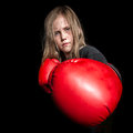 Little girl with boxing gloves a young female child looks mean as she gets ready to throw a punch at the camera wearing Stock Photo
