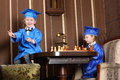 Little girl and boy in blue suits play chess