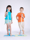 Little girl and boy with mop on white Royalty Free Stock Photo