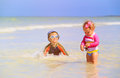 Little girl and boy playing with starfish at beach Royalty Free Stock Photo
