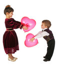 Little girl and boy with red heart-like balloons Stock Photos
