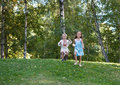 Little girl and boy running from the hill Royalty Free Stock Photo
