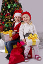 Little girl and boy sitting with gift under christmas tree smiling Stock Image