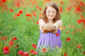 Little girl with bread young showing a wheat brad in flower field Royalty Free Stock Images