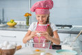 Little girl breaking eggs into bowl a glass preparing a dough Stock Photography