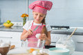 Little girl breaking eggs into bowl a glass preparing a dough Stock Images