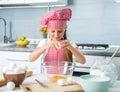 Little girl breaking eggs into bowl a glass preparing a dough Royalty Free Stock Photos