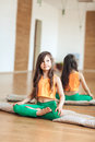 A little girl in a bright room practicing yoga, sitting on a rug, swept aside
