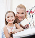 Little girl brushes teeth with her mom smiling Stock Images