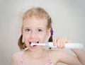 Little girl brushing her teeth with electric toothbrush Stock Images