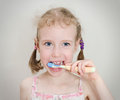 Little girl brushing her teeth with toothbrush Stock Photo