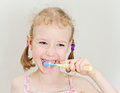 Little girl brushing her teeth with toothbrush Stock Photos