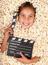 Little girl buried in popcorn with movie clapper board Stock Photo