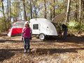 Little girl camping with teardrop trailer in the woods tent and Royalty Free Stock Photos