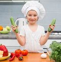 Little girl in a cap chef in the kitchen with cucumbers Stock Photos
