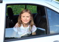 Little girl in a car smiling sitting silver looking out from window Royalty Free Stock Image