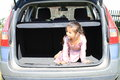 Little girl in car trunk pink dress loaded of a silver Royalty Free Stock Images