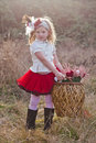 Little girl carrying large wickerwork basket pretty blonde in retro outfit of satin blouse and frilly red skirt with plants in it Royalty Free Stock Image