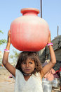 Little Girl Carrying Water Stock Images