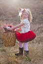 Little girl carrying wicker basket dressed in vintage outfit of satin blouse and frilly red skirt with hair decorations a across Royalty Free Stock Photo